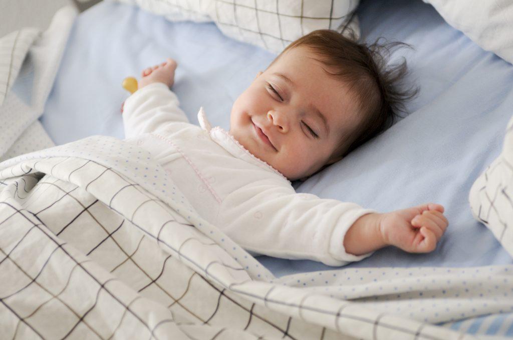 Säugling liegt lachend im Bett und streckt sich mit geschlossenen Augen