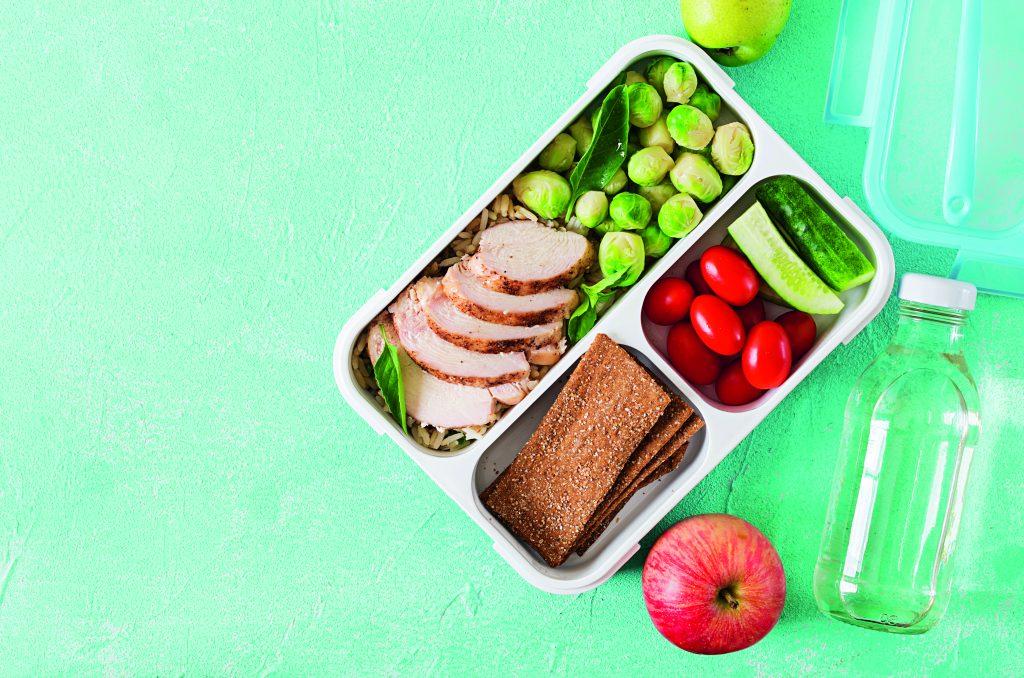Lunchbox gefüllt mit Hähnchen, Knäckebrot und verschiedenen Gemüsesorten