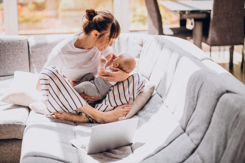 Frau sitzt mit Säugling auf dem Arm im Schneidersitzt vor einem Laptop auf dem Sofa