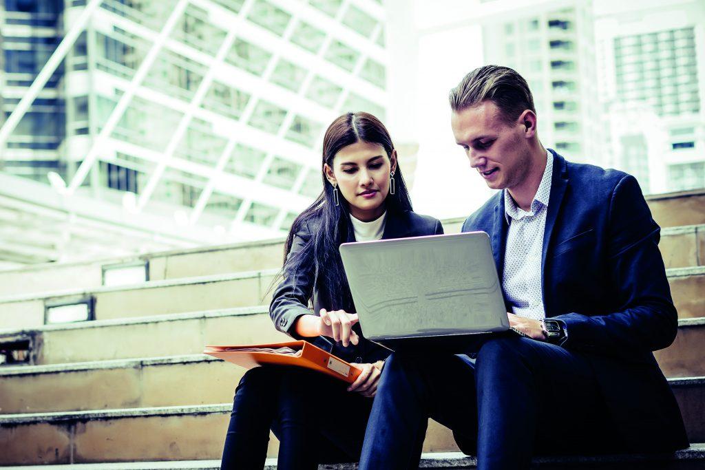 Junge Frau und ihr Arbeitskollege sitzen auf einer Treppe und schauen auf einen Laptop