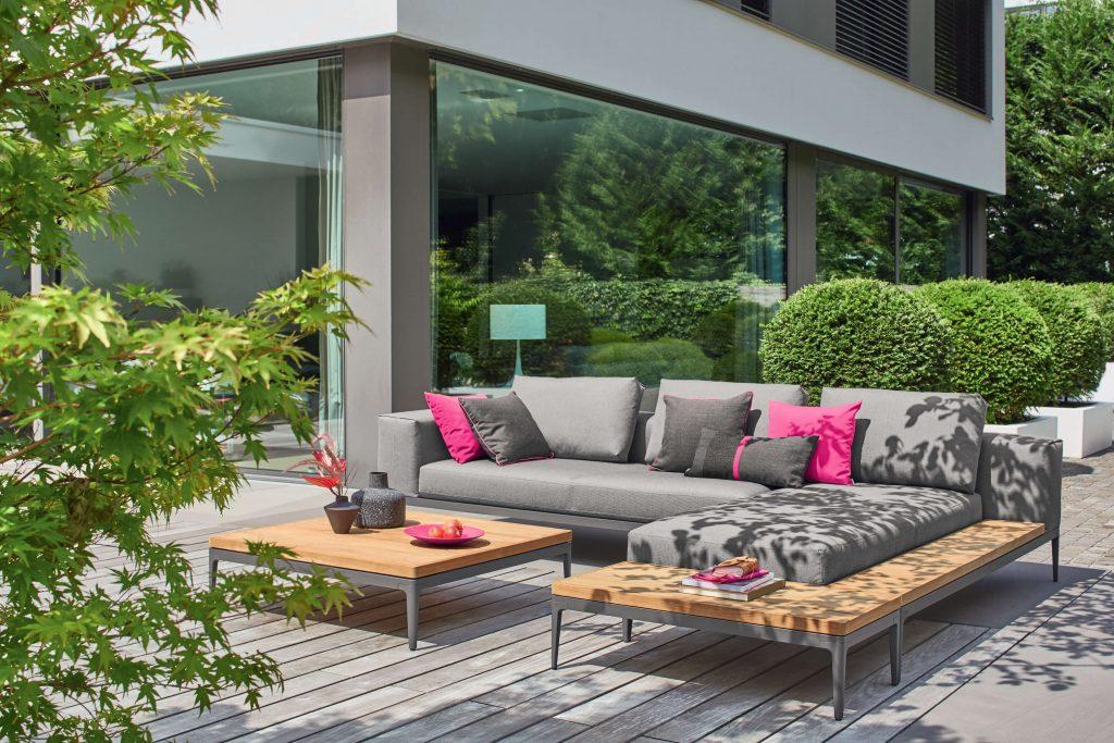 Terrasse mit grauen Loungemöbeln und pinken Kissen
