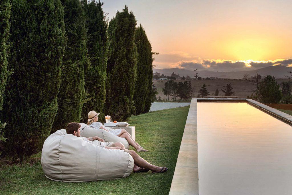 Ein junges Paar schaut sich auf Sitzsäcken am Pool den Sonnenuntergang an