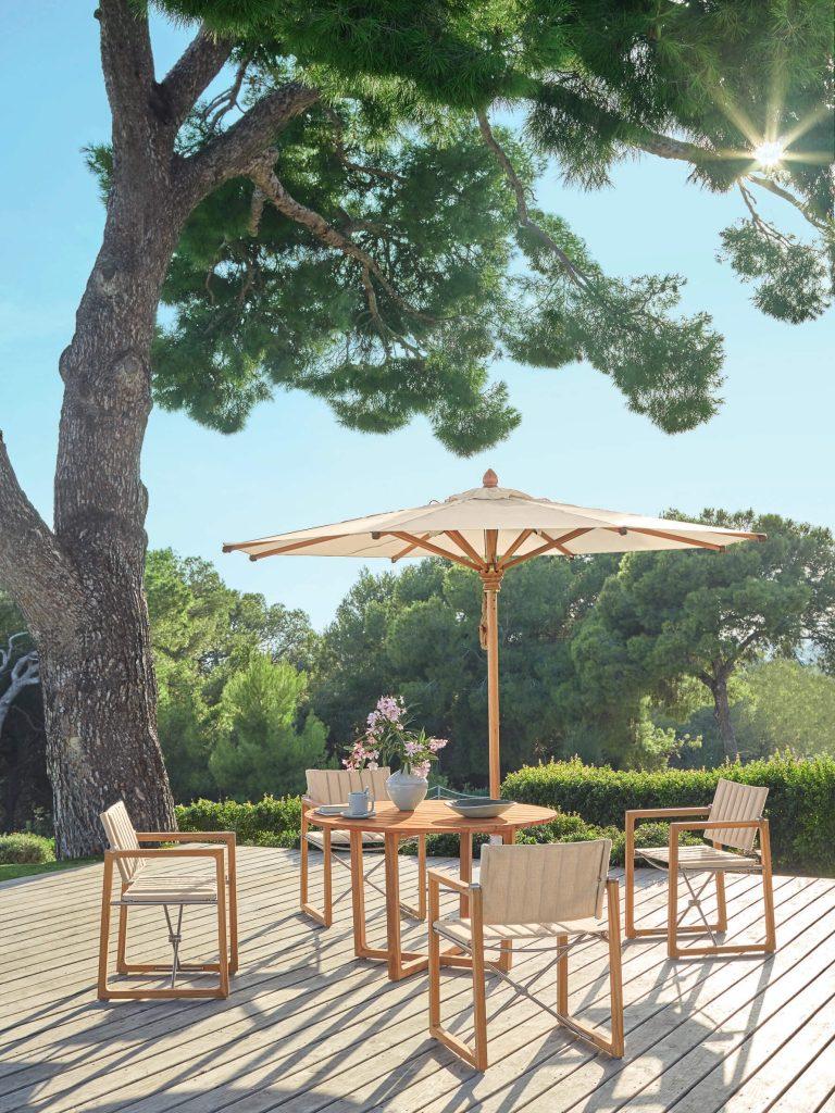 Mediterrane Terrasse mit Sitzgruppe aus Holz und Sonnenschirm