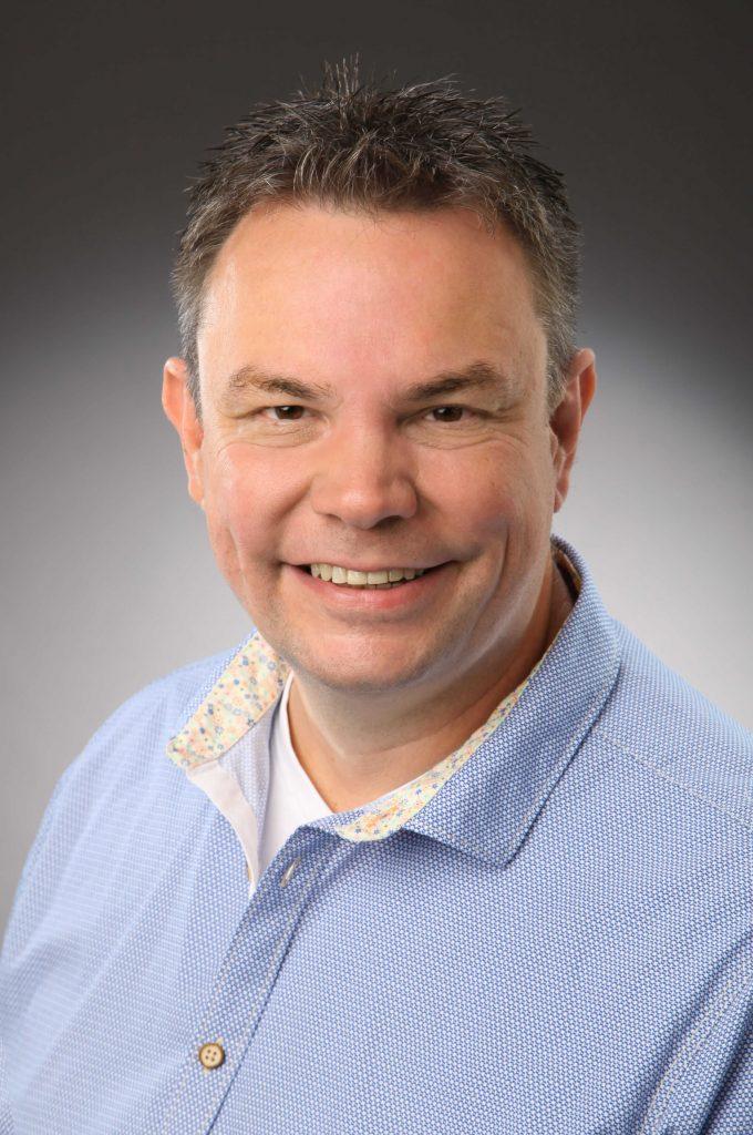 Porträt von eonem Mann in einem hellblauen Hemd