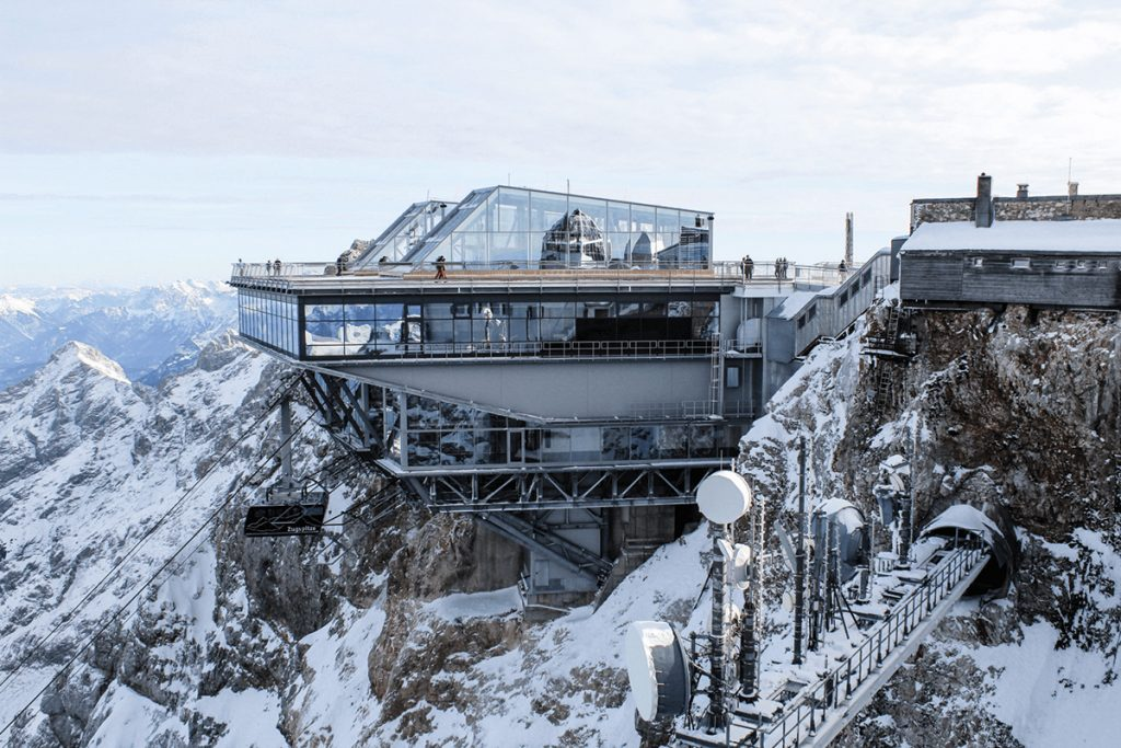 Bergbahnstation aus Glas und Metall zwuischen schneebedeckten Felsen