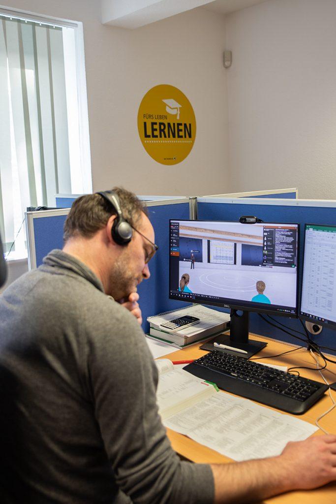 Mann sitzt mit Kopfhörern vor PC und liest in seinen Unterlagen