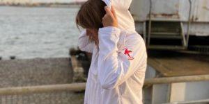 Junge Frau trägt weiße Softshelljacke mit rotem K auf Oberarm