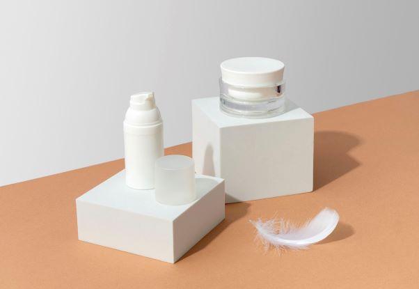 Pumpspender und Cremetiegel auf quadratischen Podesten in Weiß